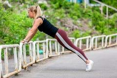E Jonge vrouw die duw UPS in de helling doen Sportief jong blondemeisje op een zonnige dag bij het stadion Het gezonde leven stock afbeeldingen
