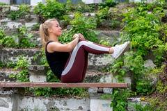E Jonge vrouw die op een bank opwarmen, die oefeningen op buikspieren doen Sportief jong blondemeisje op zonnig royalty-vrije stock fotografie