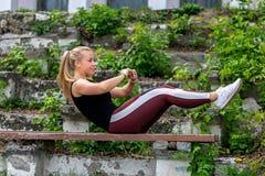 E Jonge vrouw die op een bank opwarmen, die oefeningen op buikspieren doen Sportief jong blondemeisje op zonnig royalty-vrije stock foto's
