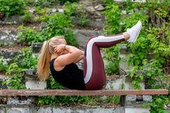 E Jonge vrouw die op een bank opwarmen, die oefeningen op buikspieren doen Sportief jong blondemeisje op zonnig stock foto