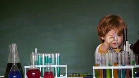 E klar skola De bar ut ett nytt experiment i kemi Lyckligt le stock video