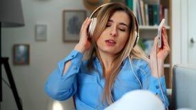 E Kobiety s?uchaj?ca muzyka w he?mofonach od zbiory wideo