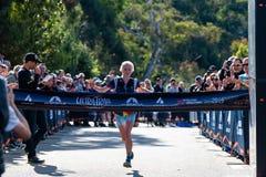 E Löpare Paige Penrose, vinnare av kvinnornas händelse, på mållinjen, omkring att korsa arkivbild