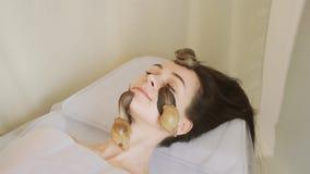 E La mujer joven en el balneario recibe un masaje facial con los caracoles Achatina r almacen de video
