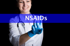 E le docteur féminin de sourire presse un doigt sur un écran virtuel NSAIDs écrit sur un virtuel image libre de droits