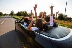 E Le groupe heureux de jeunes filles et les types s'asseyent dans la voiture tiennent leurs mains  image stock