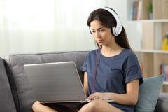 E-learning dello studente online con un computer portatile a casa immagine stock