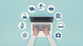 E-learning and education icons. Student connecting online with a laptop and university icons: e-learning and graduation concept stock image