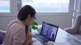 E-lerend, gebruikt het jonge vrouwelijke gebrilde passen online onderwijs voor zelfontplooiing laptop computer en maakt binnen no stock footage