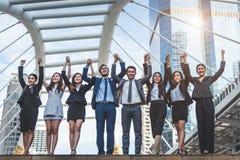 E Lyckliga affärsmän och affärskvinnor som in lyfter handen som laget royaltyfria bilder