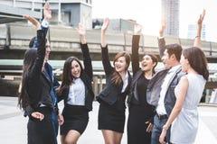 E Lyckliga affärsmän och affärskvinnor som in lyfter handen som laget arkivbild