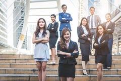 E Lyckliga affärsmän och affärskvinnor som in står som laget arkivbild