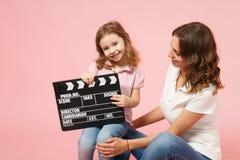 E Mère, fille de petit enfant d'isolement sur le mur rose en pastel image libre de droits