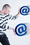 E-mail. Man pushing blue e-mail signs at white background Stock Photos