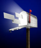 E-mail. Letters flying into a galvanized mailbox showing volume light flying out Royalty Free Stock Images