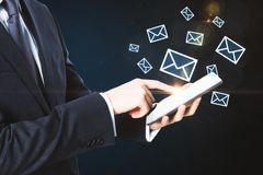 E-mail marketing concept. Side view of unrecognizable businessman hands using tablet with digital email icons on dark background. E-mail marketing concept Stock Photos