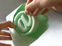 E-mail symbol. Woman's hand taking out an @ symbol of the envelope royalty free stock photography