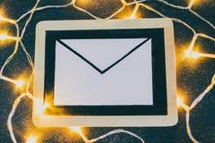 E-maildieenvelop op bord door feelichten wordt omringd stock foto