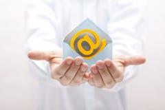 E-mailsymbool met envelop in handen Stock Afbeeldingen