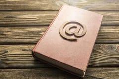 E-mailteken op een boek op een houten achtergrond stock afbeelding