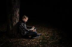 E 10 2016 - Man som läser en bok och dricker te i en tyst höstskog royaltyfri fotografi