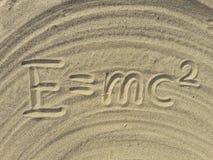 E mc2 skriver på sanden Arkivfoton