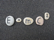 E=mc2 Theory of relativity on carved stones over lava sand. Einsteins theory on carved stones over black vulcanic sand Royalty Free Stock Photos