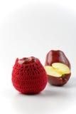 2 e 1/2 mele rosse e lavorano all'uncinetto accogliente Fotografia Stock