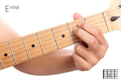 E minor guitar chord tutorial. Em - basic minor keys guitar tutorial series. Closeup of hand playing E minor chord on guitar, isolated on white background Royalty Free Stock Image