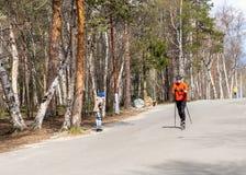 E Monchegorsk - май 2019 Тренировка спортсмена на конькобежцах ролика Езда биатлона на лыжах ролика с поляками лыжи, в стоковые фотографии rf