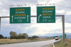 E75 motorway signs towards Athens and Kozani. Large green direction signs over a gantry royalty free stock image