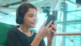 E Muchacha adolescente feliz joven en auriculares que escucha la forma de vida de la música encendido almacen de video