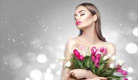 E Mulher bonita que recebe um ramalhete de tulipas coloridas fotos de stock royalty free