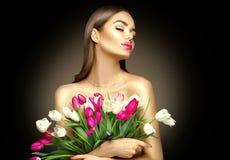 E Mulher bonita que recebe um ramalhete de tulipas coloridas imagem de stock