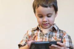E Nettes Kind, das Spiele auf Smartphone spielt stockbilder