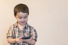 E Nettes Kind, das Spiele auf Smartphone spielt exemplar stockfotos