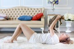 E O gato no abra?o da mulher que encontra-se no tapete de l?s Bonito imagem de stock