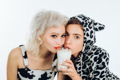 E o N?tta flickor p? mejeri bantar att dricka mj?lkar tillsammans Gulligt ungt royaltyfri foto