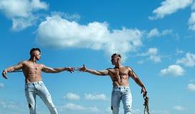 E Os homens mostram fora sua força contra concorrentes Gêmeos atléticos em lados opostos Gêmeos fotos de stock royalty free