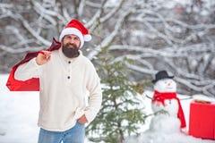 E Petit bonhomme de neige mignon et homme barbu avec le sac ? provisions Hippie Santa Claus Bonhomme de neige drôle avec des acha photo libre de droits