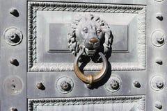 E Poignée en bronze sous forme de tête d'un lion sur la porte de palais photo libre de droits