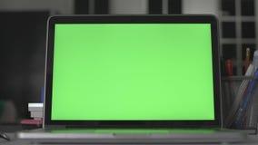 Ноутбук с зеленым экраном Темный офис Идеально разместить свое изображение или видео акции видеоматериалы