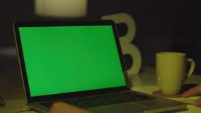 Ноутбук с зеленым экраном Темный офис Идеально разместить свое изображение или видео видеоматериал