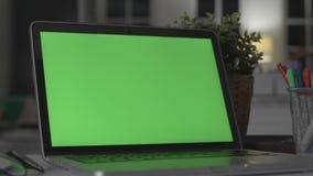Ноутбук с зеленым экраном Темный офис Идеально разместить свое изображение или видео сток-видео