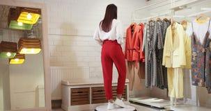 E r 在一条大衬衣和红色裤子的模型 股票视频