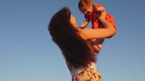 妈妈把女儿扔到天上 母亲与小孩子在蓝天对面玩 快乐的家庭 股票录像