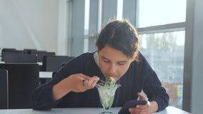 机场等飞机 少女吃沙拉,看智能手机 生活咖啡馆的互联网 终端 影视素材