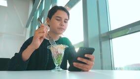 机场等飞机 少女吃沙拉,看智能手机 生活方式中的互联网咖啡馆 机场 股票视频