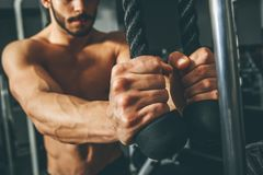 image photo : Muscular man working out in gym doing exercises with triceps rope