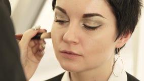 Закрыть лицо женщины при применении косметики с кистью на коже в салоне красоты Портретная красивая женщина сток-видео